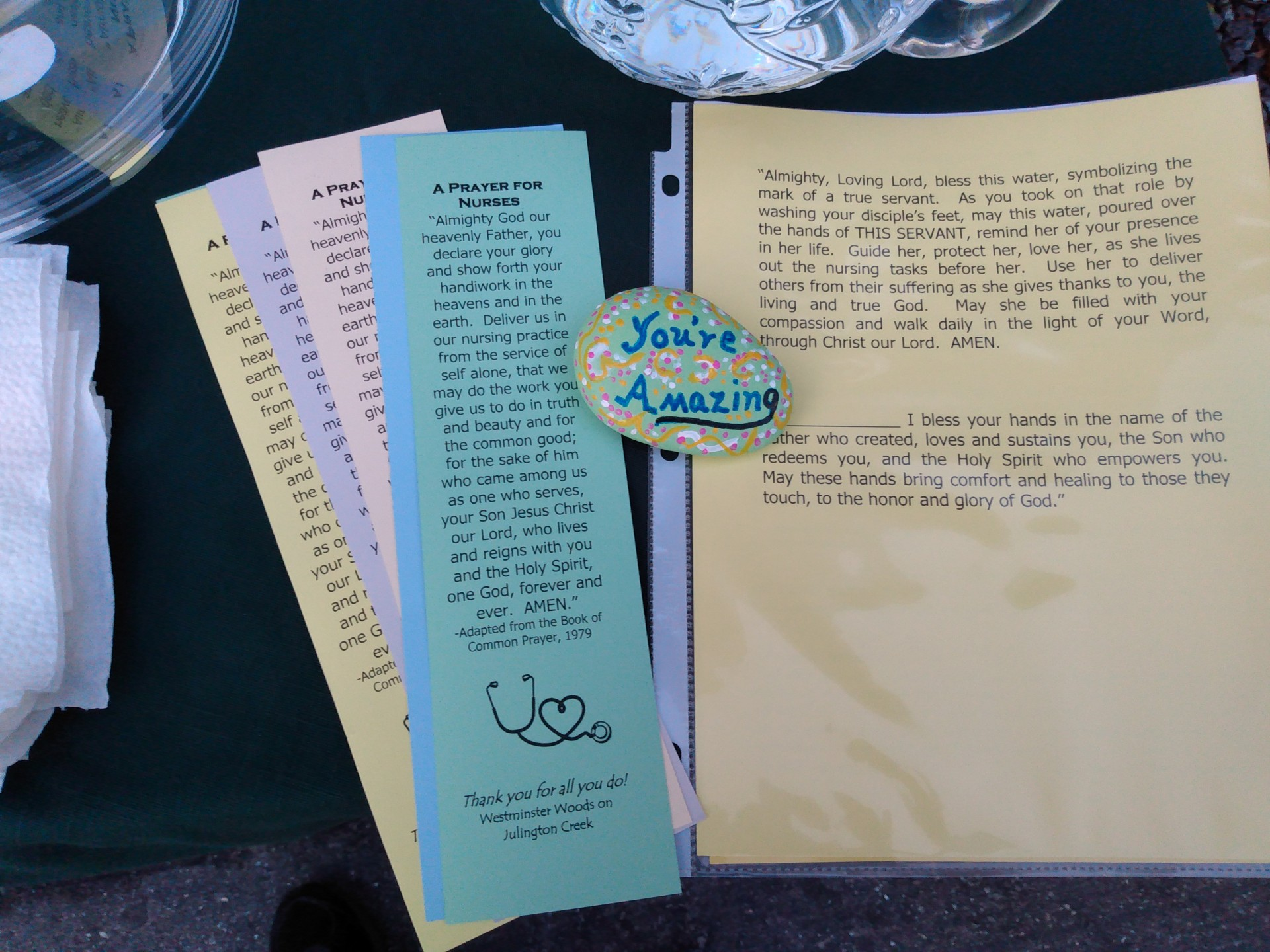 "Chaplain's cart with printed prayers to hand out and a stone painted with the saying ""You're Amazing""."