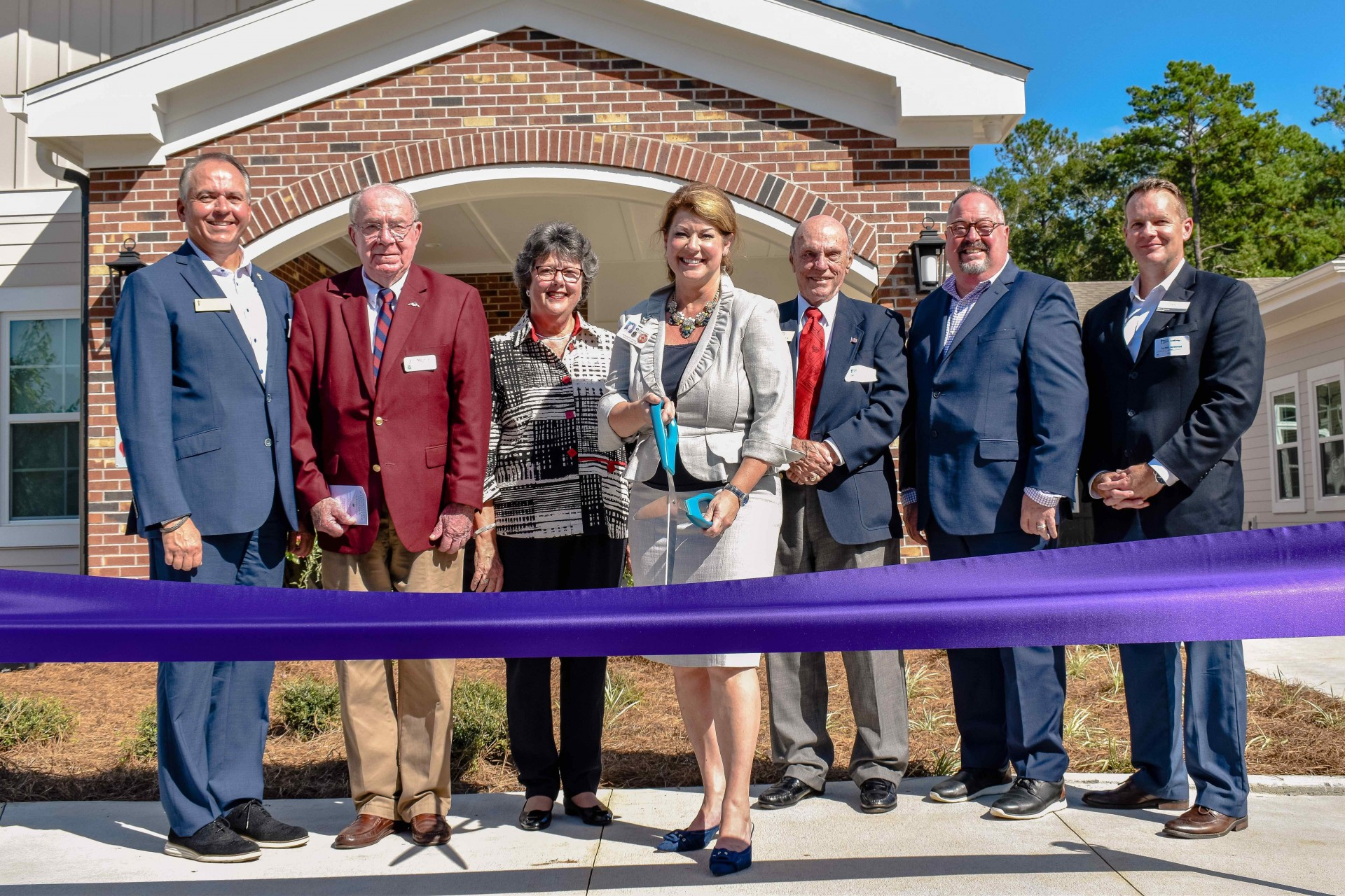 Executive Director Shannon Sauls, at center, holds the scissors for the ceremonial ribbon-cutting. (From left) Westminster Communities of Florida CEO Terry Rogers, Westminster Oaks Resident Council President James Melton, Board Member Linda Shelley, Sauls, Board Member John Milton V, Chief Operating Officer Garry D. Hennis, and LeadingAge Florida President Steve Bahmer.
