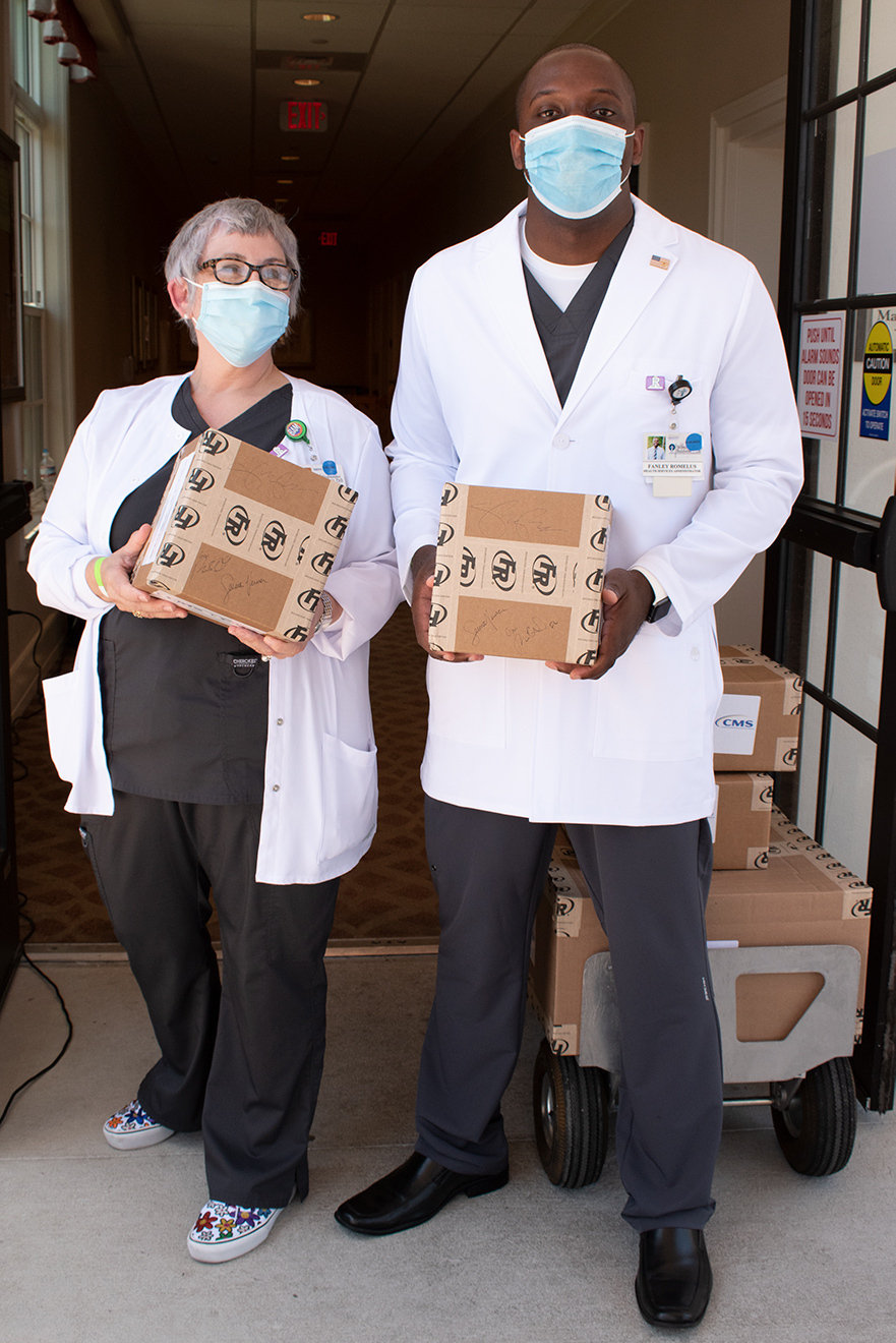 From left, Shirley Schultz, Director of Nursing, and Fanley Romelus, Health Services Administrator, hold boxes of personal protective equipment signed by Vice President Pence, Governor DeSantis and Administrator Verma.